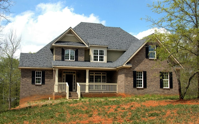 Front view of a home with asphalt shingle roof and brown bricks.