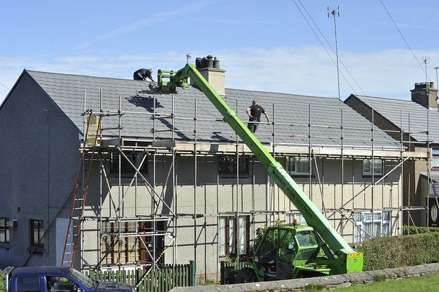 House with scaffold and roofers working on the roof.